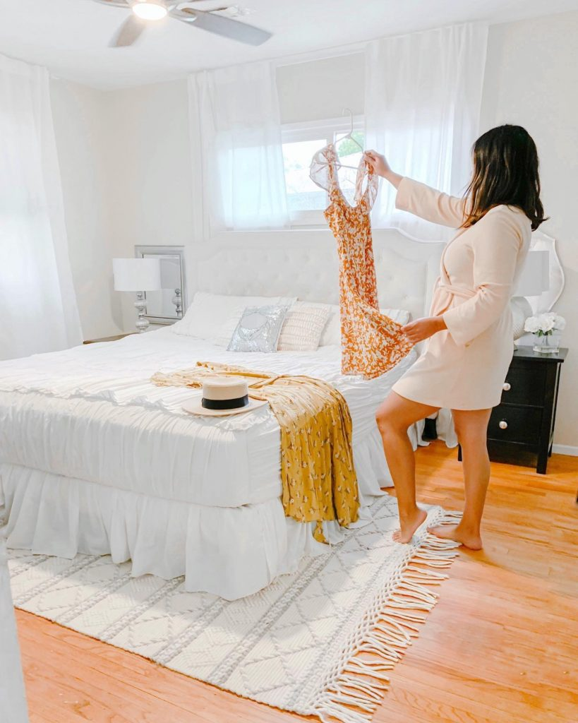 girl in master bedroom standing near bed with white bedding and tufted headboard