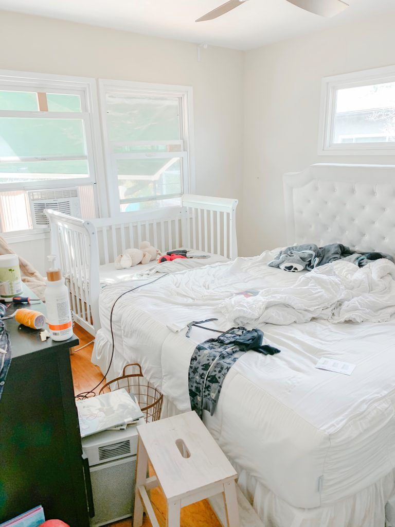 master bedroom with white bedding, tufted headboard and white wool tassel rug