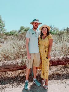 couple hugging in meadow girl wearing yellow summer dress and hat