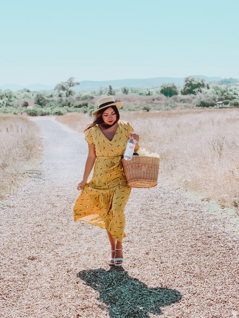 Girl in meadow in summer yellow dress and hat with a picnic basket