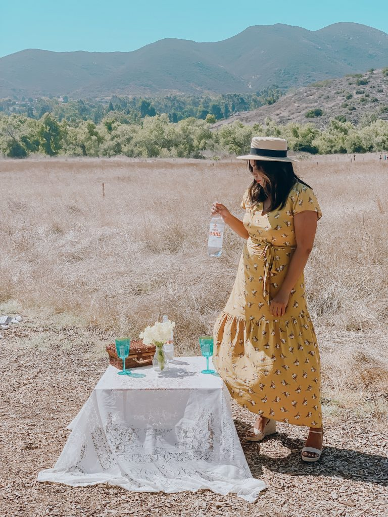 Girl in meadow in yellow summer dress and hat having a picnic