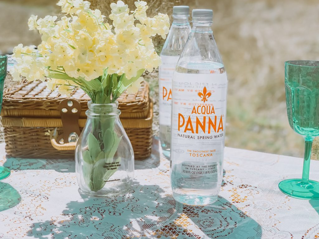 Bottled water at picnic table with flowers and basket